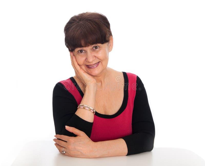 65 anni del ritratto della donna contro di fondo bianco Bella donna che sorride, Londra di età di pensionamento immagini stock libere da diritti