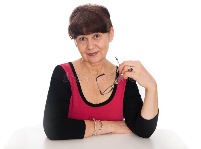 65 anni del ritratto della donna contro di fondo bianco Bella donna che sorride, Londra di età di pensionamento immagine stock