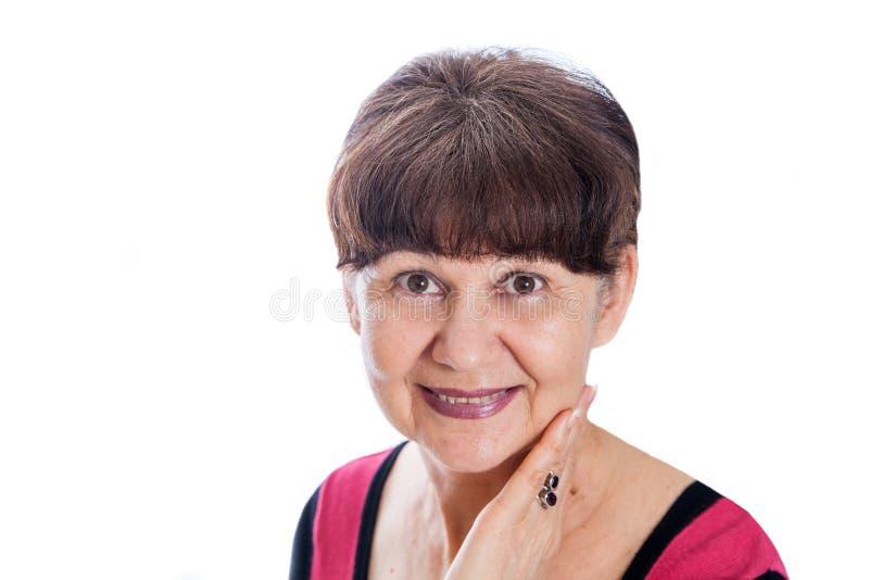 65 anni del ritratto della donna contro di fondo bianco Bella donna che sorride, Londra di età di pensionamento fotografie stock