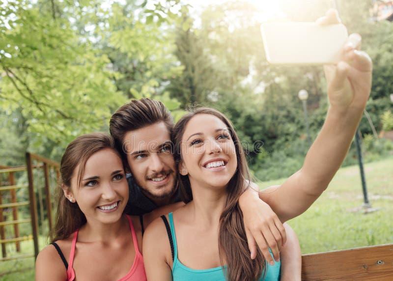 Anni dell'adolescenza allegri al parco che prende i selfies fotografia stock