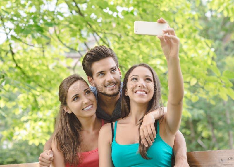 Anni dell'adolescenza allegri al parco che prende i selfies fotografia stock libera da diritti