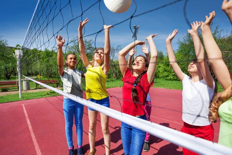 Anni dell'adolescenza che giocano attivamente vicino alla rete di pallavolo fotografia stock