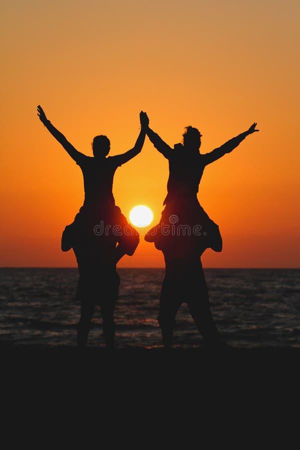 Anni dell'adolescenza che si siedono sulle spalle degli amici nel tramonto immagini stock libere da diritti