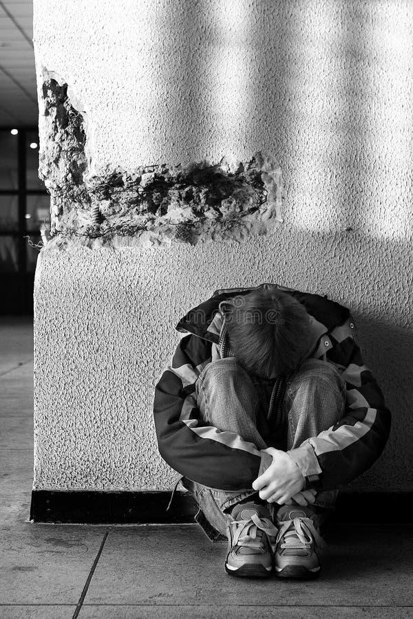 Anni dell'adolescenza del ragazzo che si siedono sul pavimento da solo in città fotografia stock