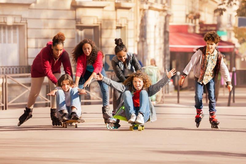 Anni dell'adolescenza divertendosi rollerblading e pattinare immagini stock libere da diritti