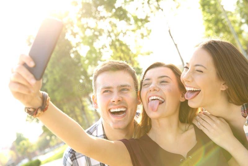 Anni dell'adolescenza divertenti che prendono selfie e scherzare immagine stock libera da diritti