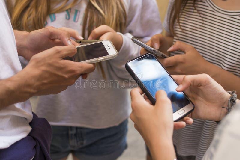 Anni dell'adolescenza facendo uso dei telefoni cellulari fotografia stock