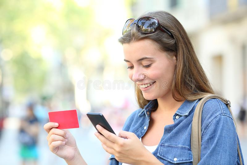 Anni dell'adolescenza felici che comprano online con uno smartphone nella via immagini stock