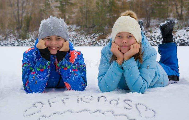 Anni dell'adolescenza felici che luing nella neve Amici dell'iscrizione immagine stock