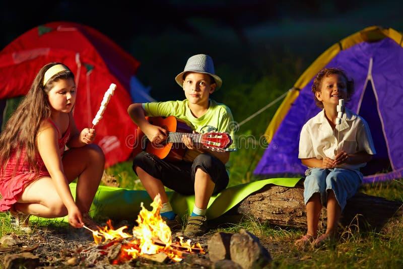 Anni dell'adolescenza felici intorno al fuoco di accampamento di notte immagine stock libera da diritti