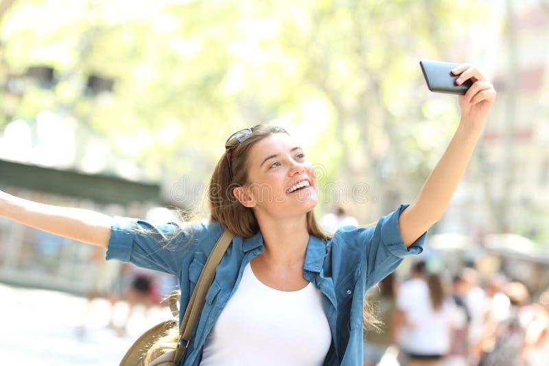 Anni dell'adolescenza millenari felici che prendono i selfies nella via immagini stock libere da diritti