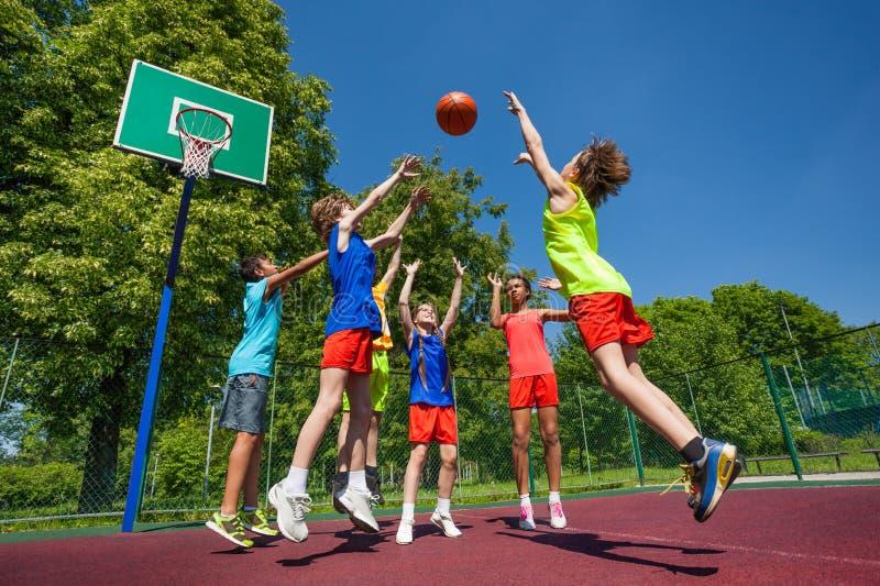 Anni dell'adolescenza nel salto che gioca insieme gioco di pallacanestro fotografie stock libere da diritti