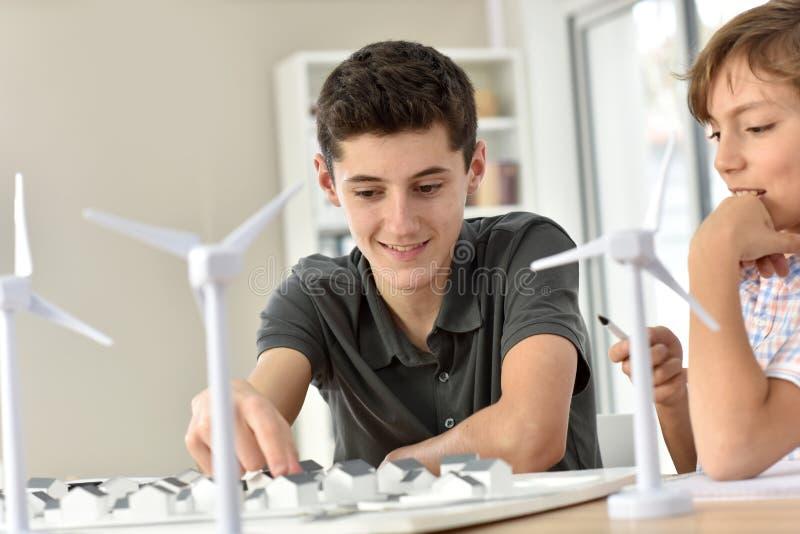 Anni dell'adolescenza nella classe che impara circa le risorse naturali di energia immagini stock