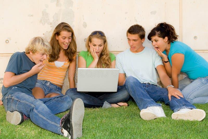 Anni dell'adolescenza scossi con il computer portatile fotografie stock