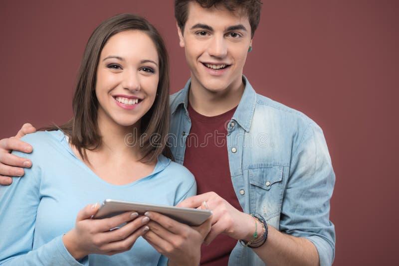 Anni dell'adolescenza sorridenti facendo uso di una compressa digitale fotografia stock