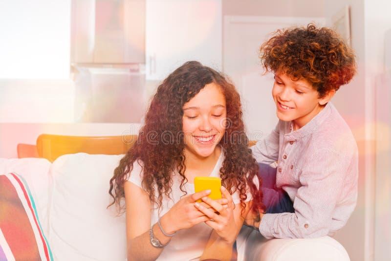 Anni dell'adolescenza svegli che chiacchierano facendo uso del telefono cellulare all'interno immagini stock