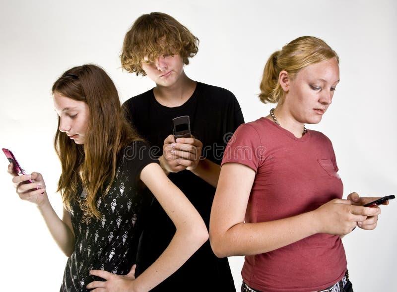 Anni dell'adolescenza Texting sul telefono delle cellule fotografia stock libera da diritti