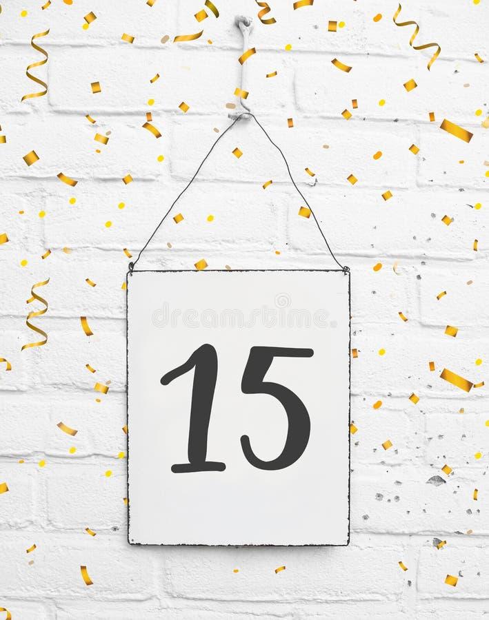 15 anni della carta della festa di compleanno con il numero quindici con dorato immagini stock