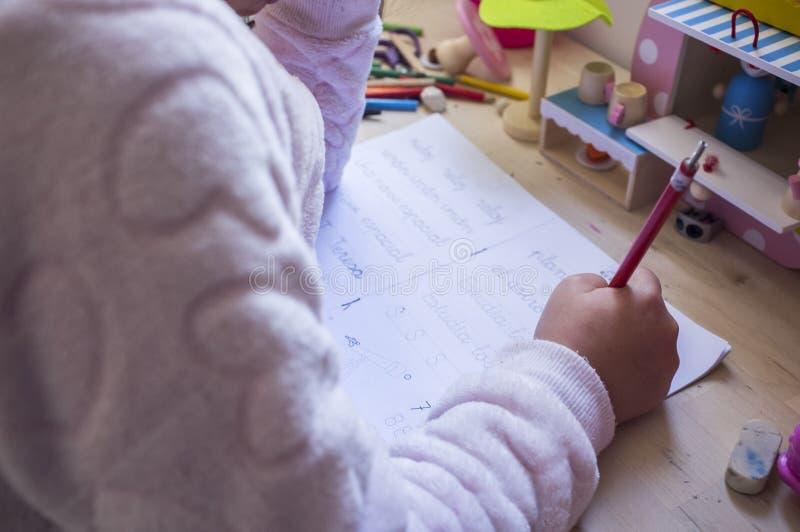 6 anni della ragazza del bambino che fa scrivendo compito nella sua stanza fotografia stock