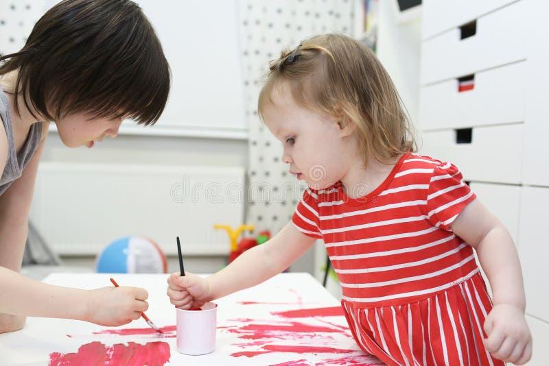 5 anni di fratello e 2 anni di sorella che dipinge a casa immagine stock