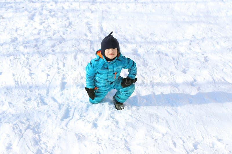 5 anni di ragazzino in camice caldo blu all'aperto nell'inverno immagini stock libere da diritti