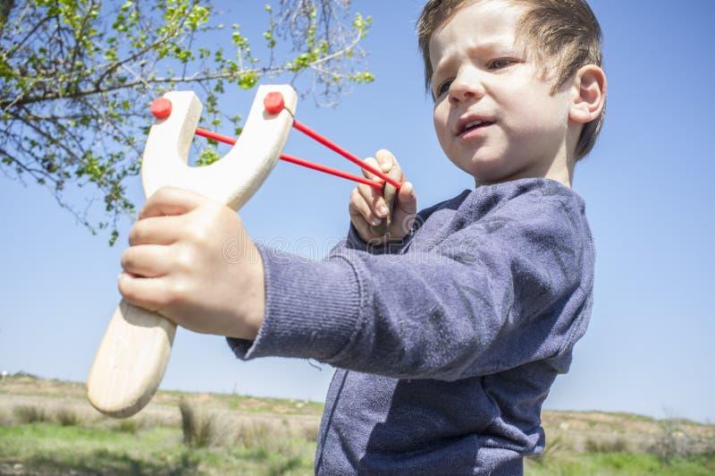 3 anni di ragazzino che spara fionda di legno fotografia stock