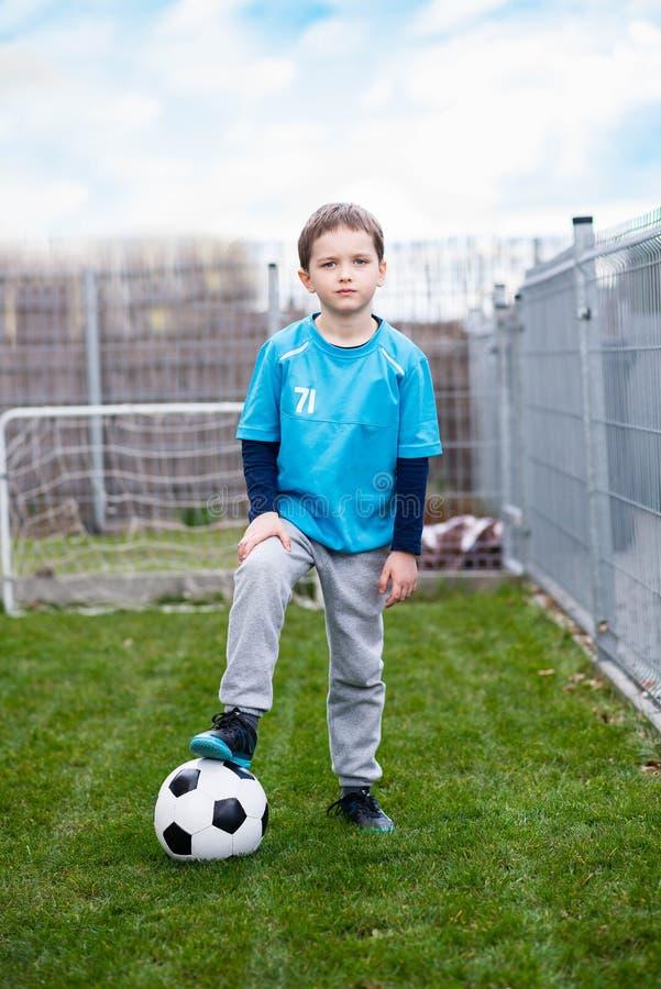 7 anni di ragazzo - calciatore con i suoi piedi sulla palla di calcio immagini stock