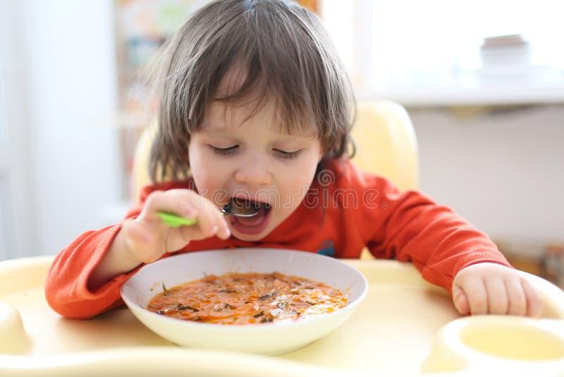 2 anni di ragazzo che mangia la minestra della rosso-barbabietola della minestra fotografia stock libera da diritti