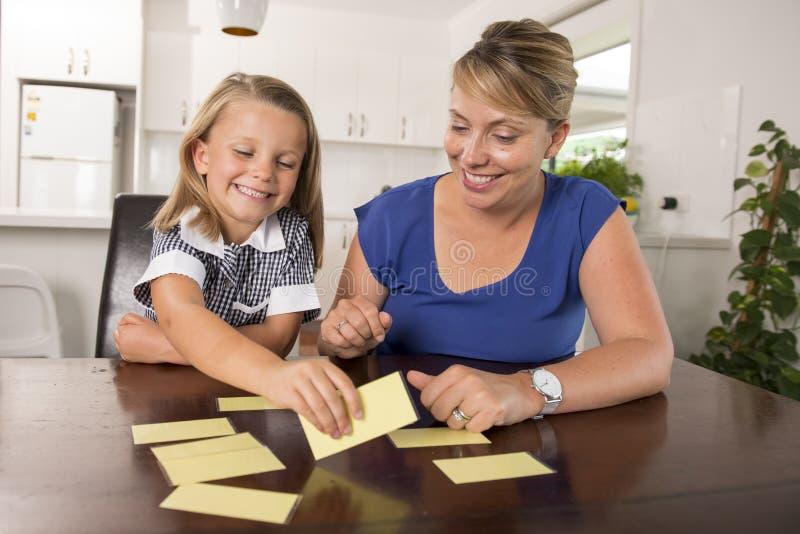 6 anni dolci e felici adorabili della figlia che impara lettura con la cucina del gioco di parole del flash card a casa che gioca immagini stock