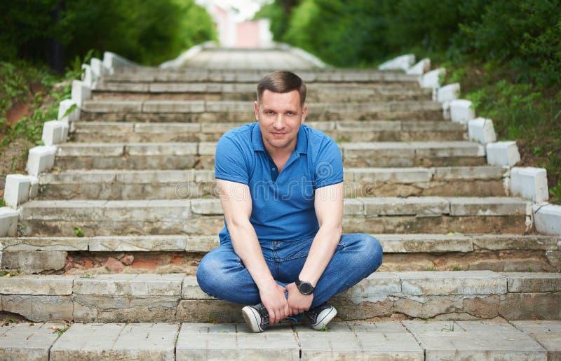 40 anni, un uomo è seduto su una scala nel parco immagine stock