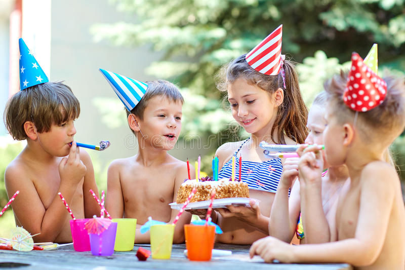 Anniversaire avec des enfants dans des chapeaux pendant l'été photographie stock