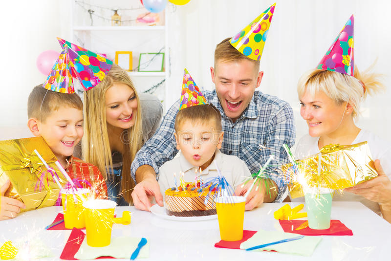 Anniversaire Le petit garçon souffle des bougies sur le gâteau d'anniversaire image stock
