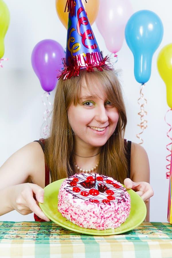 Anniversaire. Une jeune fille attirante avec le gâteau photo libre de droits