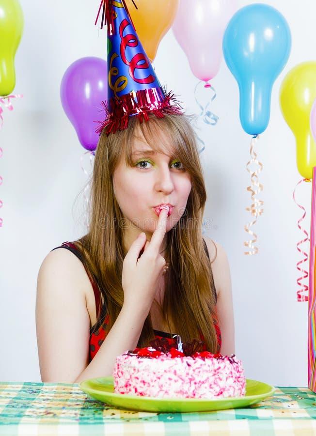 Anniversaire. Une jeune fille attirante mangeant le gâteau photo stock