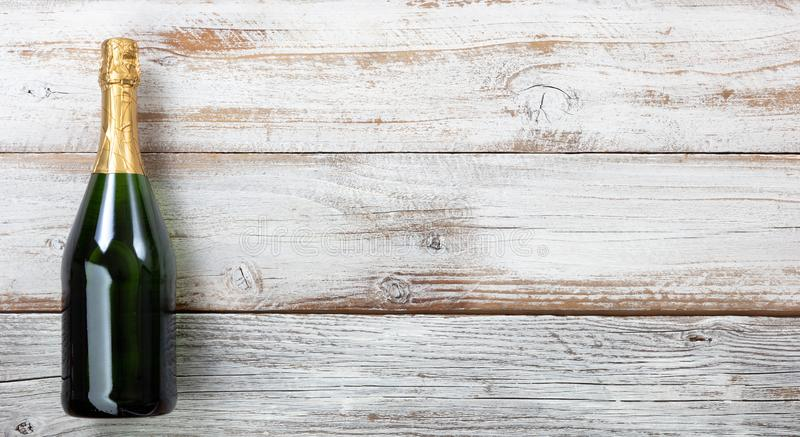 Anniversary background with a bottle of champagne on white weathered wood stock photography