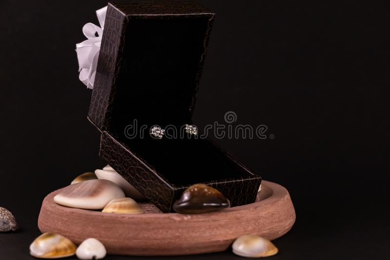 Anniversary gift concept. Beautiful diamond earings in leather gift box and spreaded seashells on black ground royalty free stock images