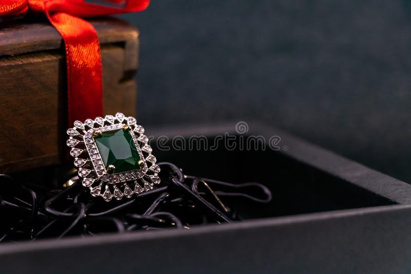 Anniversary gift concept. Close-up of Emerald ring in black box and wooden gift box with red ribbon on black background stock images
