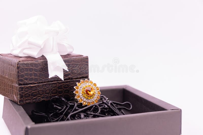 Anniversary gift concept. Cocktail ring in black box and lather gift box decorated with ribbon on white background royalty free stock photos