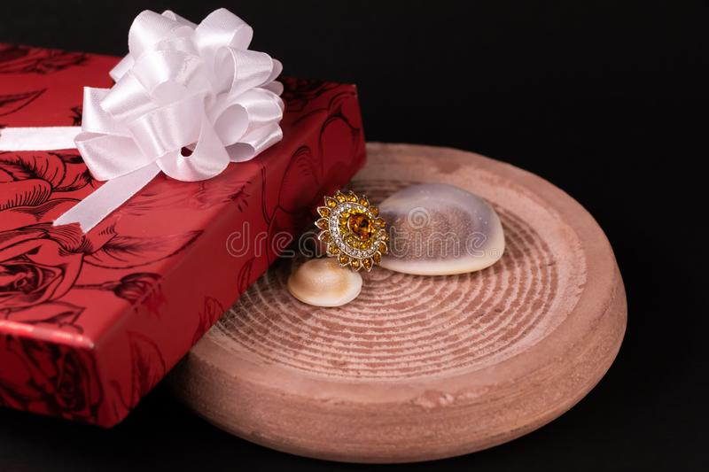 Anniversary gift concept. Cocktail ring with decorated red giftbox and seashell on sand stone with dark background stock photo