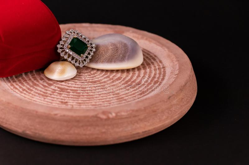 Anniversary gift concept. Emerald ring and red gift box with seashell on sand Stone with black background royalty free stock photography