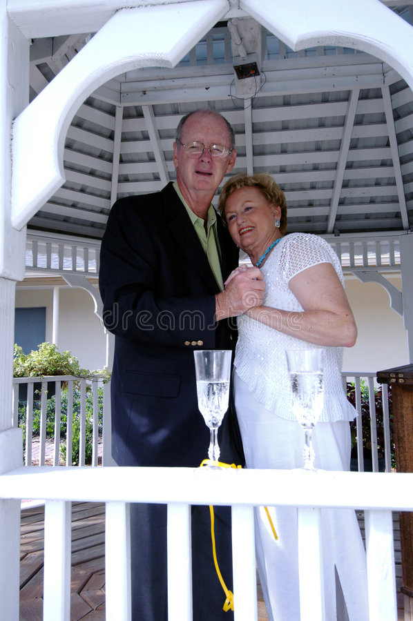 Anniversary party. A senior couple dancing during an anniversary or wedding party in a gazebo