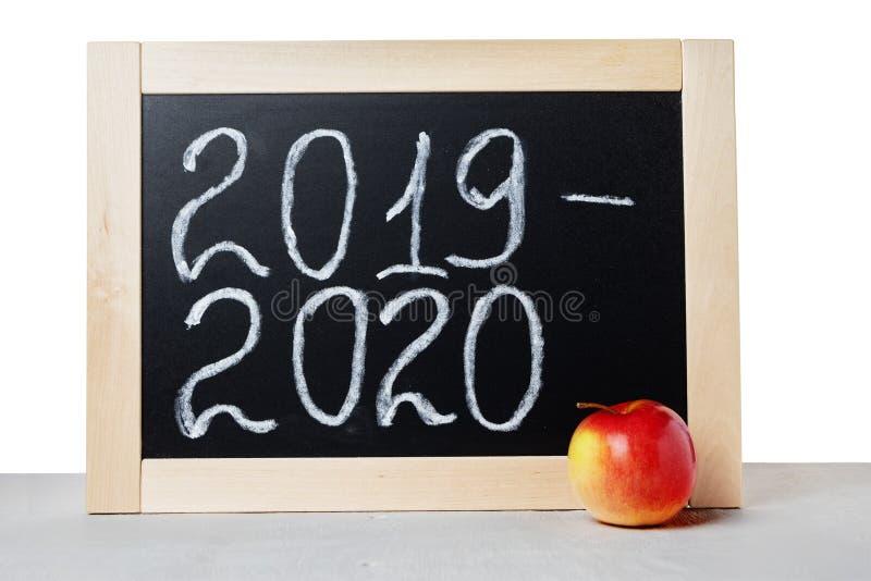 Anno accademico 2019 2020 Lavagna e mela della scuola del fondo sulla tavola, isolata su fondo bianco immagine stock libera da diritti