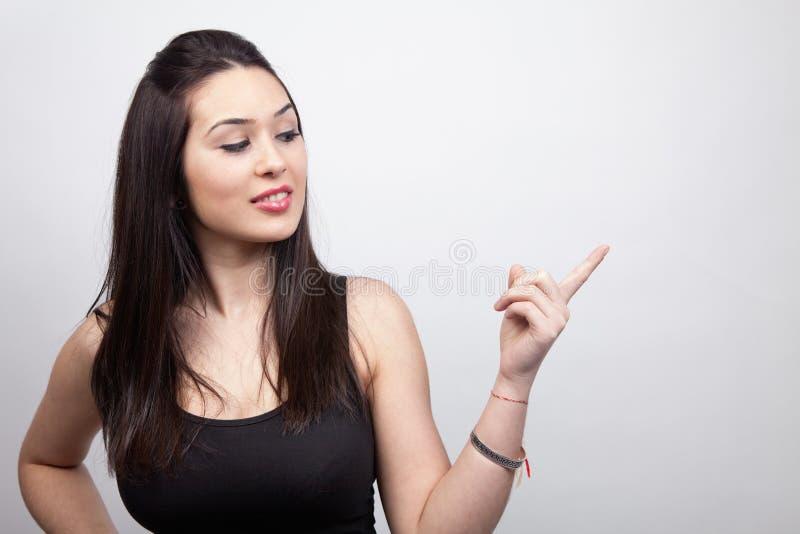 Annoncez - la jeune femme mignonne affichant quelque chose photos stock