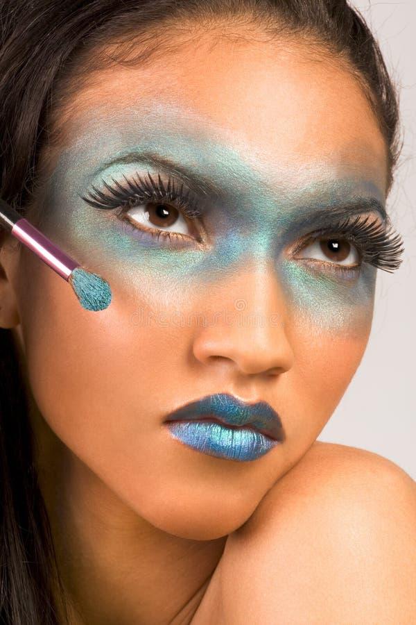 annonsera blått exotiskt gör den blandade racen upp kvinna arkivfoto