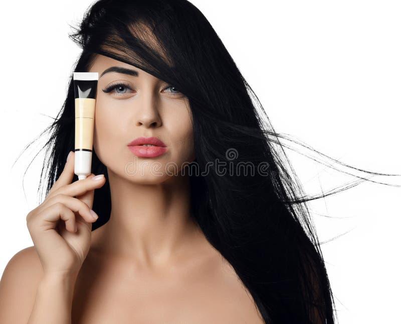 Annonseringbegreppsslut upp av kvinnabrunetten med hår som fladdrar i vinden som visar det lilla röret av kräm på ett vitt arkivbilder