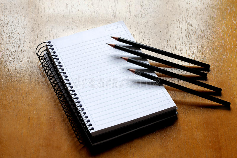 Annotation. Notebook on wooden table with four pencils stock photo