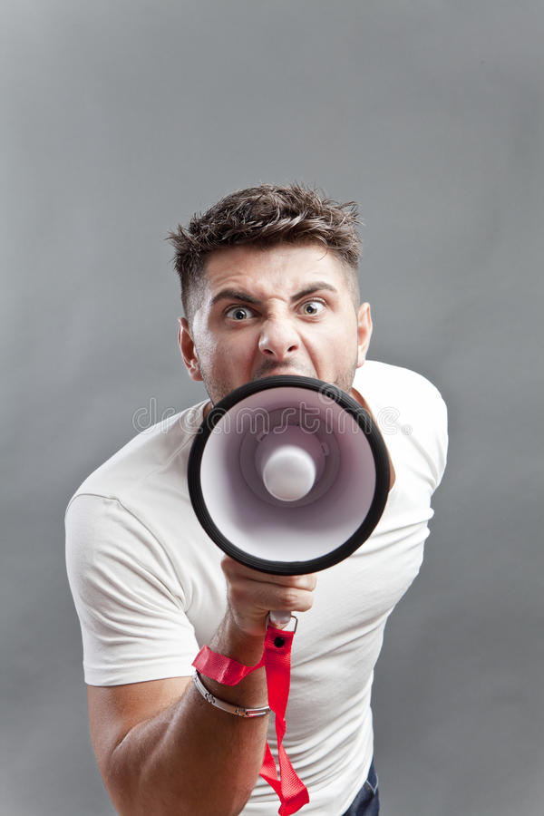 Announcement. Young man yelling and making announcement over a megaphone stock photo