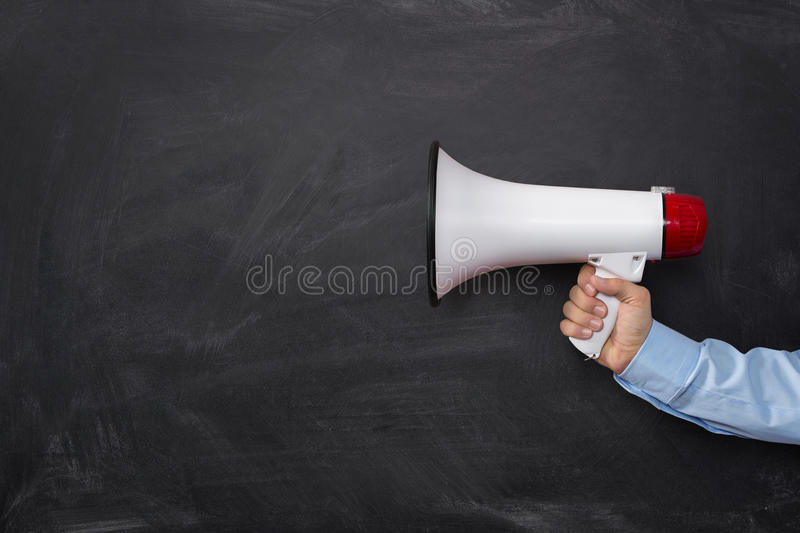 Announcement. Close up of businessman's hand holding megaphone over chalkboard background with copy space stock photos