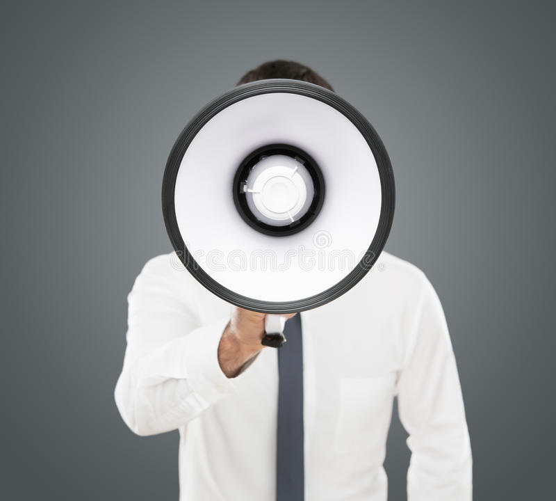 Announcement. Young businessman shouting on the megaphone isolated on gray background royalty free stock image