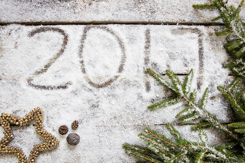 Announcing 2017 on winter snow background for holiday, top view royalty free stock image